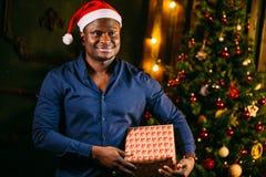 Individuo afroamericano con la sonrisa encantadora que celebra el regalo de la Navidad en manos Foto de archivo