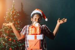 Individuo afroamericano con la sonrisa encantadora que celebra el regalo de la Navidad en manos Imagen de archivo