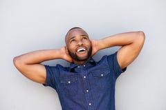 Individuo afroamericano hermoso que sonríe con las manos detrás de la cabeza Fotos de archivo libres de regalías