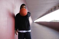 Individuo afroamericano que lleva una sudadera con capucha negra que lleva a cabo un baloncesto mientras que se coloca en una ace imagenes de archivo