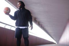 Individuo afroamericano que lleva una sudadera con capucha negra que lleva a cabo un baloncesto mientras que se coloca en una ace imagen de archivo libre de regalías