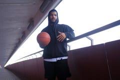 Individuo afroamericano que lleva una sudadera con capucha negra que lleva a cabo un baloncesto mientras que se coloca en una ace fotografía de archivo libre de regalías