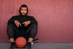 Individuo afroamericano que lleva una sudadera con capucha negra que se sienta en un monopatín y que lleva a cabo un baloncesto m fotos de archivo