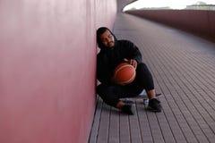 Individuo afroamericano que lleva una sudadera con capucha negra que se sienta en un monopatín y que lleva a cabo un baloncesto m imagenes de archivo