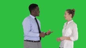 Individuo afroamericano y muchacha que hablan del negocio en una pantalla verde, llave de la croma almacen de video