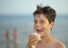 Individuo agradable mientras que come un bocadillo en la playa Fotos de archivo