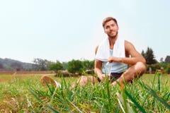 Individuo agradable que se sienta en hierba Fotos de archivo libres de regalías
