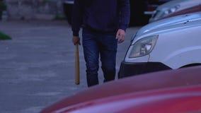 Individuo agresivo que camina con el bate de béisbol para castigar a sus delincuentes, vandalismo almacen de metraje de vídeo