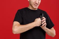 Individuo agresivo que golpea su puño en un teléfono móvil que lo rompe imágenes de archivo libres de regalías