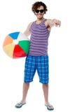 Individuo alegre con la pelota de playa que señala en usted Foto de archivo