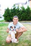 Individuo alegre en un paseo en el parque en un día de verano con su perro de Jack Russell Son llenos de alegría, sonriendo, divi imágenes de archivo libres de regalías