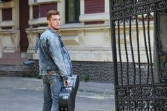Individuo alegre joven con el pelo rojo en la puerta con una guitarra en el caso fotos de archivo libres de regalías