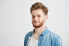 Individuo alegre joven en auriculares que sonríe mirando la cámara que escucha fluir música sobre el fondo blanco Imagen de archivo libre de regalías