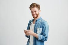 Individuo alegre joven en auriculares que sonríe sosteniendo el teléfono que mira la cámara que escucha la música sobre el fondo  Imagen de archivo