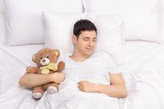 Individuo alegre que duerme con un oso de peluche Fotos de archivo
