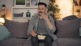 Individuo alegre que mira señalar de risa de la TV en la pantalla y la consumición de las palomitas en casa almacen de video