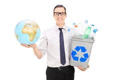Individuo amistoso de Eco que sostiene la papelera de reciclaje y un globo Fotografía de archivo libre de regalías
