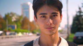 Individuo asiático del og hermoso de la cara del primer que mira la cámara relajada y la situación cerca de la carretera, vida de almacen de metraje de vídeo