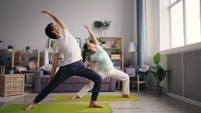 Individuo asiático hermoso que entrena en casa con la novia que hace la yoga que se coloca en la estera almacen de metraje de vídeo