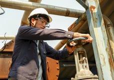 Individuo asiático que lleva un casco que gira la válvula del tubo de agua en el proceso de producción imagen de archivo libre de regalías