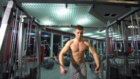 Individuo atlético hermoso que hace pectorals en el instructor de la cruce en el gimnasio Front View metrajes