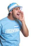 Individuo atractivo con el jersey argentino y sombrero que gritan para su equipo Foto de archivo libre de regalías
