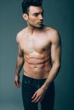 Individuo atractivo joven muscular que presenta en estudio en vaqueros Fotos de archivo