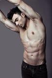 Individuo atractivo joven muscular que presenta en estudio en vaqueros Imagen de archivo libre de regalías