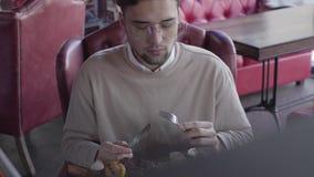 Individuo atractivo que se sienta en restaurante de lujo y plato delicioso impresionante eatting con la carne y las verduras asad almacen de video