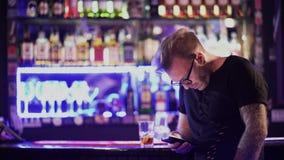 Individuo barbudo atractivo con los vidrios que mandan un SMS en su teléfono celular mientras que se coloca en el contador de la  almacen de video