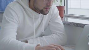Individuo barbudo atractivo elegante joven del retrato en una camiseta blanca y el mecanografiar en un ordenador portátil mientra almacen de metraje de vídeo