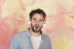 Individuo barbudo hermoso americano con los auriculares Forma de vida musical Canciones que escuchan adolescentes alegres de DJ v fotos de archivo