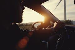 Individuo barbudo joven del inconformista que se sienta detrás de la rueda del coche alquilado durante su viaje anticipado el vac fotografía de archivo