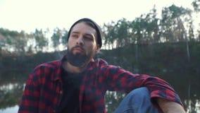 Individuo barbudo joven sentarse en el bosque cerca del río y del cigarro marrón que fuma Hombre brutal con una barba negra en un metrajes