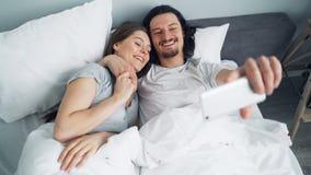 Individuo barbudo que toma el selfie en cama con la novia que usa la cámara del smartphone almacen de metraje de vídeo