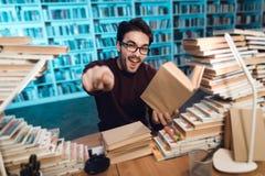 Individuo blanco rodeado por los libros en biblioteca El estudiante es emocionalmente libro de lectura fotografía de archivo