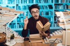 Individuo blanco rodeado por los libros en biblioteca El estudiante es emocionalmente libro de lectura foto de archivo