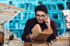 Individuo blanco rodeado por los libros en biblioteca El estudiante es libro de lectura fotografía de archivo
