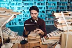 Individuo blanco rodeado por los libros en biblioteca El estudiante está utilizando la tableta fotos de archivo libres de regalías
