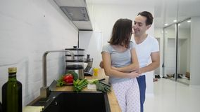 Individuo cariñoso que abraza a su novia sonriente en su cocina temprano por la mañana con el desayuno que es hecho en la cámara  almacen de video
