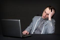 Individuo caucásico cansado que se sienta delante del ordenador fotos de archivo libres de regalías