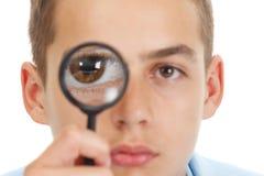 Individuo caucásico que mira a través de una lupa aislada en blanco Foto de archivo