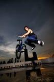Individuo chino asi?tico de la bicicleta que hace un truco en tejado Fotografía de archivo libre de regalías