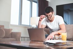 Individuo chocado que trabaja en el ordenador en casa foto de archivo libre de regalías