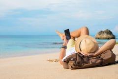 Individuo con el smartphone que miente en la playa fotos de archivo
