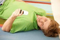 Individuo con el teléfono celular en suelo Fotos de archivo