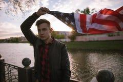 Individuo con el vuelo de la bandera de los E.E.U.U. en el viento Fotos de archivo libres de regalías