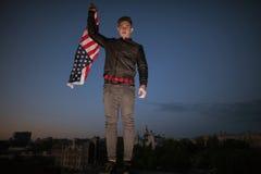 Individuo con la bandera del vuelo de los E.E.U.U. en la ciudad de la noche Foto de archivo
