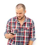 Individuo con la barba que busca su teléfono elegante para un número fotografía de archivo