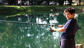 Individuo con la caña de pescar en las orillas de la pesca de lago Fotos de archivo